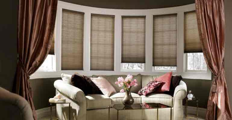 Adjustable honeycomb shades in living room bow window.