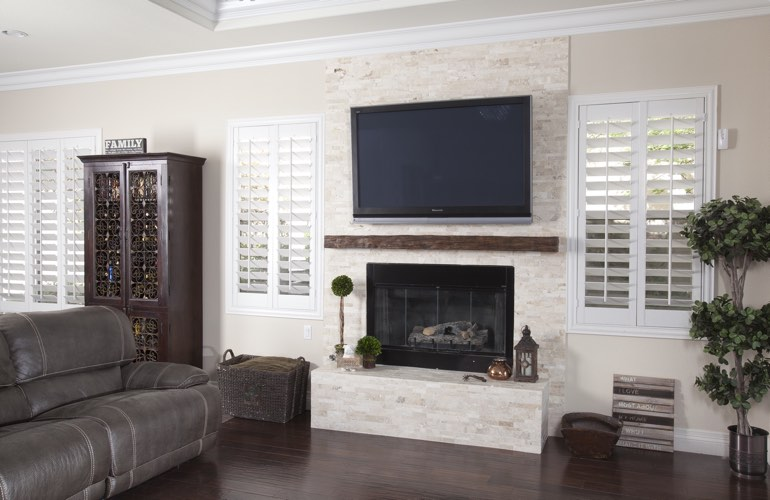 White plantation shutters in a Las Vegas living room with plank hardwood floors.