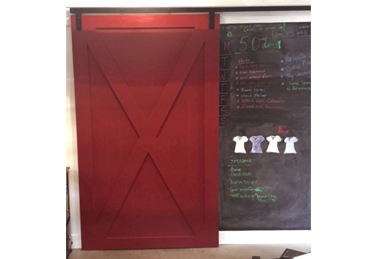 Red sliding barn door with black hardware next to chalkboard 🚪