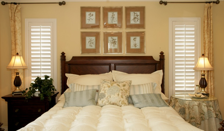 Beige bedroom with white plantation shutters covering windows in Las Vegas