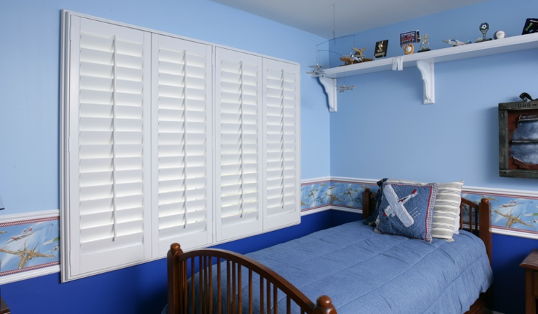 Large plantation shutters covering window in blue kids bedroom in Las Vegas