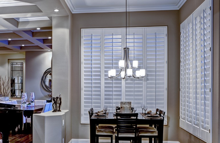 White plantation shutters on two walls of modern dining room